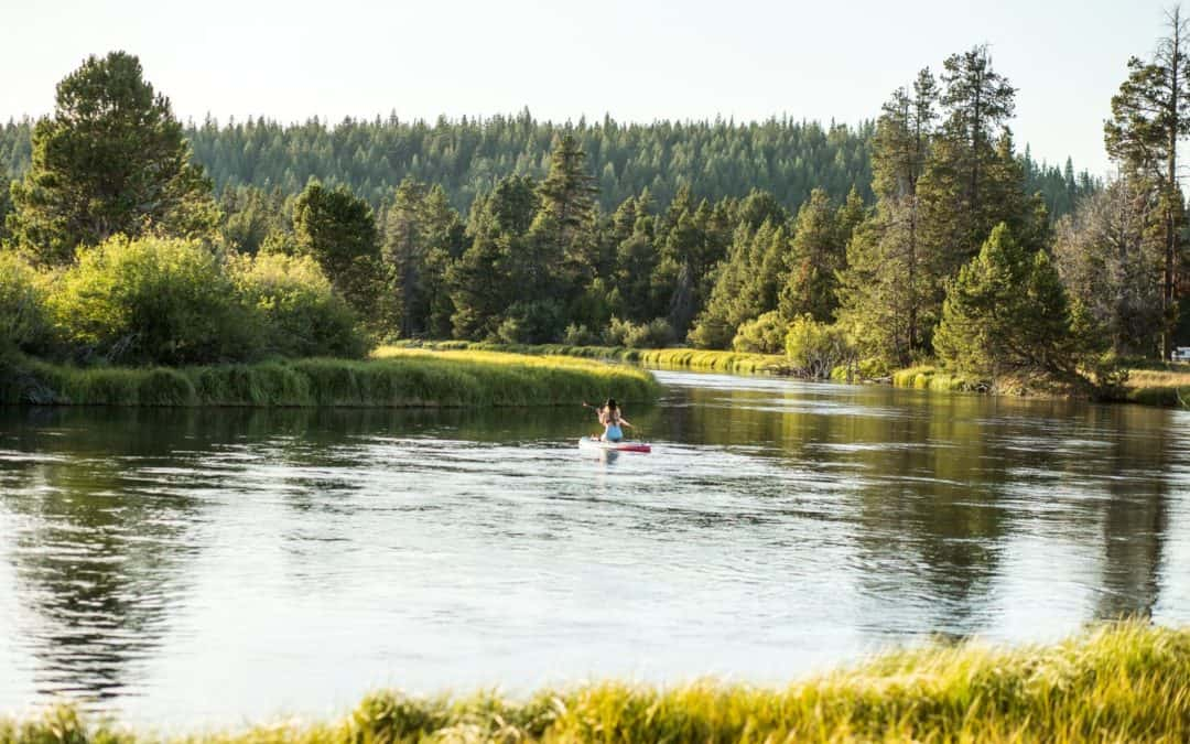 A woman kneels on a standup paddle board on the Deschutes River in Sunriver, Oregon.