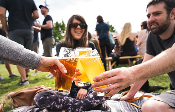 A group of people toast their beers in the outdoor seating area at Crux Fermentation Project in Bend, Oregon.