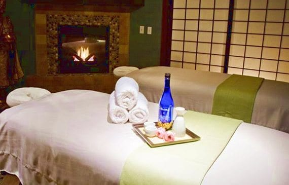 Two massage tables sit in front of a fireplace at Jinsei Spa in Bend, Oregon.