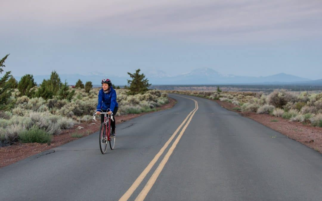 A woman rides a bike along a road with the Cascade Mountains in the background near Bend, Oregon.