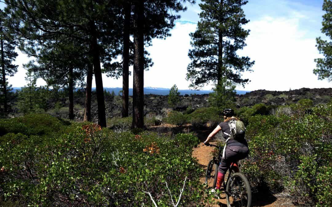 A woman rides a mountain bike through lava fields and trees near Bend, Oregon.