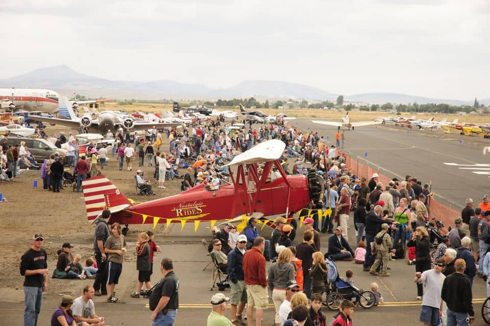 A crowd of people gather around vintage airplanes during the Airshow of the Cascades in Madras, Oregon.