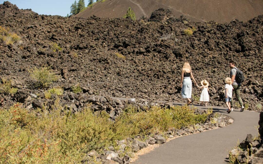 Family of four walks on pathway at Lava Lands near Bend, Oregon