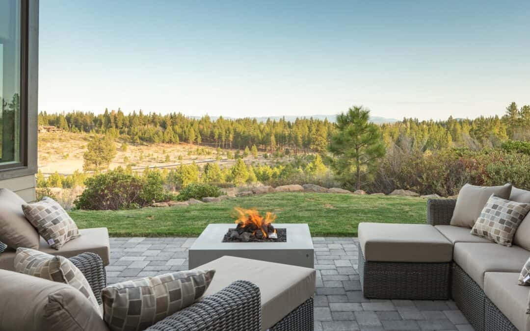 a view of the pines and mountain tops and with the comforts of a fire pit and lounger from the patio
