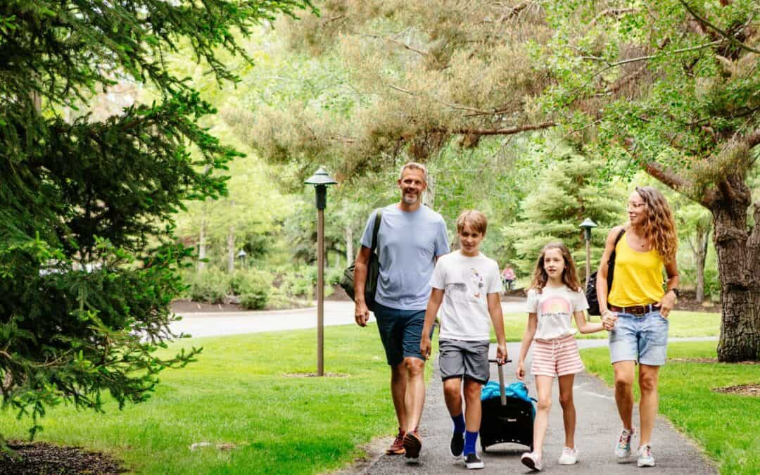 Family of four walks on paved path with luggage at Sunriver Resort