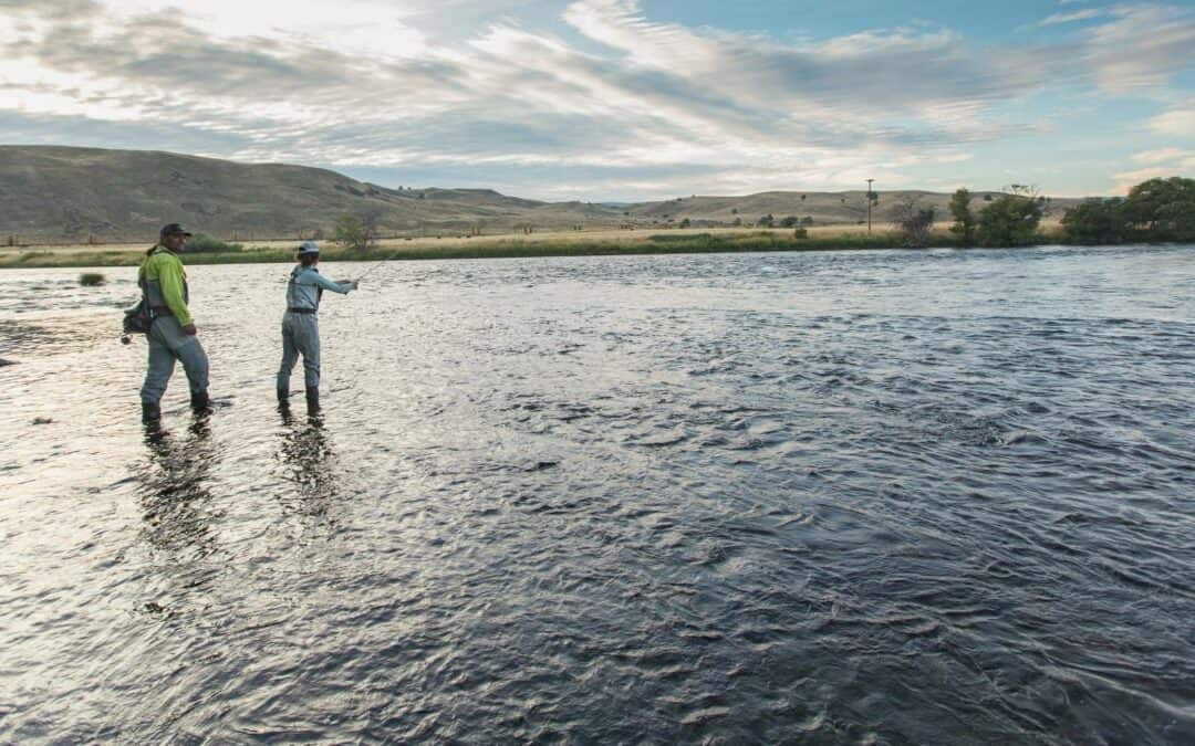 Man and woman fly fish on the banks of the river in Warm Springs, Oregon.